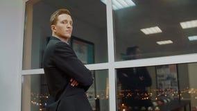 Nadenkende bedrijfsleider gekruiste handen die nieuw idee op vensterachtergrond denken stock footage