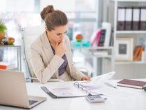 Nadenkende bedrijfsvrouwendocumenten in bureau Stock Foto