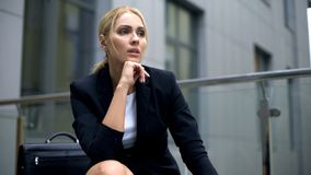 Nadenkende blonde onderneemsterzitting op bank, problemen of spanning op het werk royalty-vrije stock afbeeldingen