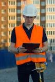 Nadenkende bouwer in weerspiegelend vest en helm die blauwdruk bekijken royalty-vrije stock foto