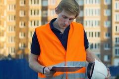 Nadenkende bouwer in weerspiegelend vest en helm die blauwdruk bekijken stock foto's