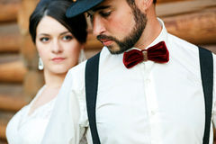 Nadenkende bruidegom in hoed met baard, snor, vlinderdas en bretels Bruid die witte huwelijkskleding dragen Gangsterstijl Stock Fotografie