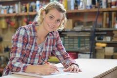 Nadenkende craftswoman nemende nota's in workshop royalty-vrije stock foto's