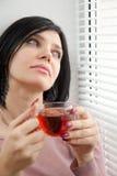 Nadenkende donkerbruine meisje het drinken thee Stock Afbeeldingen