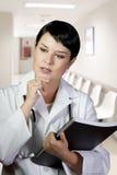 Nadenkende donkerbruine vrouwelijke arts op plicht Stock Afbeeldingen