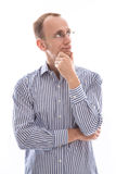 Nadenkende geïsoleerde jonge mens in een blauw overhemd en glazen royalty-vrije stock afbeeldingen