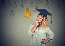 Nadenkende gediplomeerde student die in GLB-toga omhoog gloeilamp bekijken royalty-vrije stock fotografie