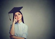 Nadenkende gediplomeerde studentenvrouw die in GLB-toga omhoog denkend kijken royalty-vrije stock afbeelding