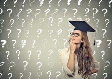 Nadenkende gediplomeerde studentenvrouw met vele vraagtekens boven hoofd stock foto's