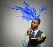 Nadenkende het boek kleurrijke plonsen die van de zakenmanlezing hoofd naar voren komen Royalty-vrije Stock Afbeeldingen