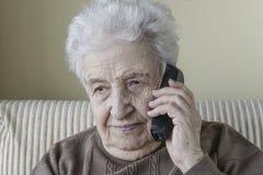 Nadenkende hogere vrouw op telefoon Stock Fotografie