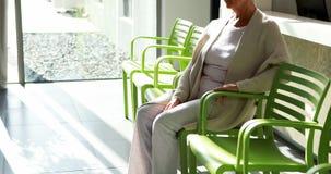 Nadenkende hogere vrouwenzitting op stoel in hal stock video