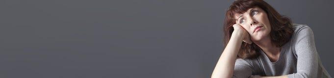 Nadenkende jaren '50vrouw die gedeprimeerde, grijze lange banner kijken Royalty-vrije Stock Fotografie