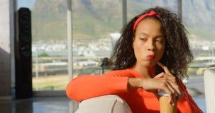 Nadenkende jonge Afrikaanse Amerikaanse vrouwelijke uitvoerende zitting op de bank in bureau 4k stock video