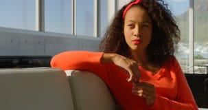 Nadenkende jonge Afrikaanse Amerikaanse vrouwelijke uitvoerende zitting op de bank in bureau 4k stock footage