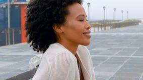 Nadenkende jonge Afrikaanse Amerikaanse vrouwenzitting op bank bij promenade stock videobeelden
