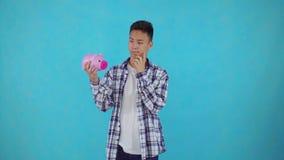 Nadenkende jonge Aziatische mens die een spaarvarken op blauwe achtergrond houden stock video