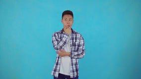 Nadenkende jonge Aziatische mens op blauwe achtergrond stock footage