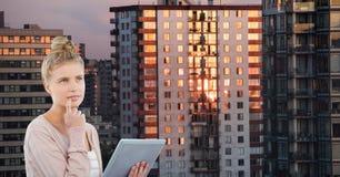 Nadenkende jonge de tabletpc van de vrouwenholding in stad stock foto's