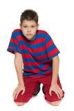 Nadenkende jonge jongen in gestreept overhemd op de vloer Royalty-vrije Stock Afbeelding