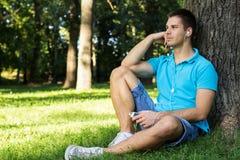 Nadenkende jonge mens die aan muziek luistert Stock Foto's