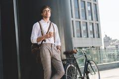 nadenkende jonge mens die met koffie om te gaan en uitstekende fiets weg op dak kijken van royalty-vrije stock foto
