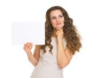 Nadenkende jonge vrouw die leeg document houden Royalty-vrije Stock Afbeeldingen