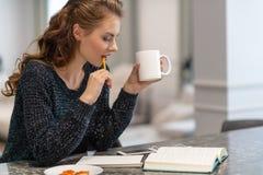Nadenkende jonge vrouw die nota's maken die blocnote in keuken gebruiken stock foto's