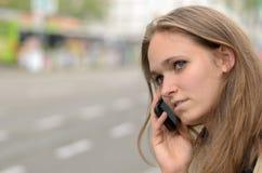 Nadenkende jonge vrouw die op mobiel haar spreken Stock Foto's