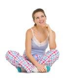 Nadenkende jonge vrouw die in pyjama's op vloer zitten Royalty-vrije Stock Foto