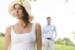 Nadenkende jonge vrouw die weg met de mens op achtergrond park bekijken Stock Afbeeldingen