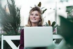 Nadenkende jonge vrouw in glazen die een computer met behulp van, die op een bank in een stadspark zitten Het concept tijd is bin royalty-vrije stock afbeelding