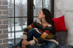 Nadenkende jonge vrouw in sweaterzitting op de vensterbank en stock foto's