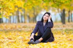 Nadenkende jonge vrouwenzitting ter plaatse onder de herfstbladeren in een bebost park die omhoog in de lucht met ernstig staren royalty-vrije stock foto