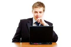Nadenkende jonge zakenman achter de computer stock afbeeldingen