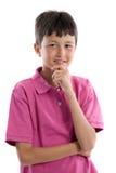 Nadenkende jongen met roze kleren stock fotografie