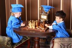 Nadenkende jongens in het blauwe schaak van het kostuumsspel royalty-vrije stock foto's