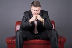 Nadenkende kerel in een kostuumzitting op een rode laag Stock Foto's