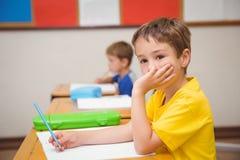 Nadenkende leerlingszitting bij zijn bureau stock afbeeldingen