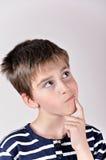 Nadenkende leuke jonge jongen die omhoog kijken Royalty-vrije Stock Foto's