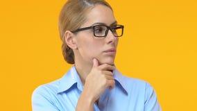 Nadenkende manager wat betreft kin en het ophalen van schouders, die naar ideeën zoeken stock footage