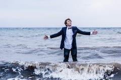 Nadenkende Mens die zich bij het Overzees met Open Wapens bevinden Royalty-vrije Stock Fotografie