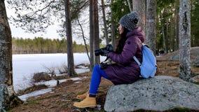 Nadenkende mooie vrouw die beelden in het hout van sneeuw behandelde aard nemen stock video