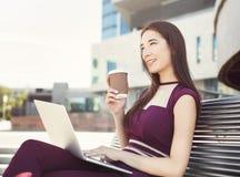 Nadenkende onderneemster die met laptop in openlucht werken Stock Foto's