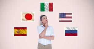Nadenkende onderneemster die zich door vlaggen tegen beige achtergrond bevinden royalty-vrije stock foto