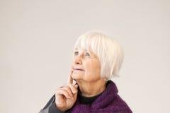 Nadenkende oude vrouw die omhoog kijkt Stock Foto's
