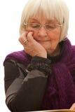 Nadenkende oudere vrouw die een boek leest Stock Foto