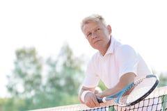 Nadenkende rijpe het tennisracket van de mensenholding terwijl het leunen op netto tegen duidelijke hemel royalty-vrije stock foto's