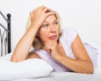 Nadenkende rijpe vrouw in slaapkamer Stock Foto's