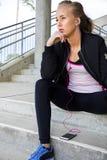 Nadenkende Sportieve Vrouw het Luisteren Muziek terwijl het Zitten op Stappen Royalty-vrije Stock Foto's